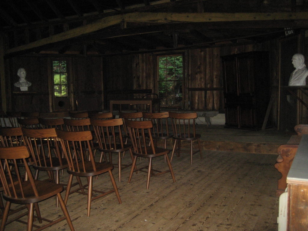 old-fashioned classroom with rows of wooden chairs